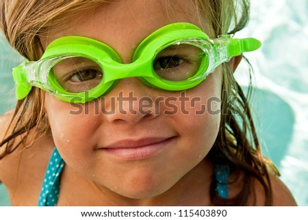 Close up of a little girl with bright green swimming goggles