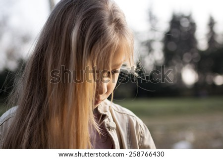 Close-up of a little girl with long hair, standing alone, head bowed, looking down with a sad expression on her face. - stock photo