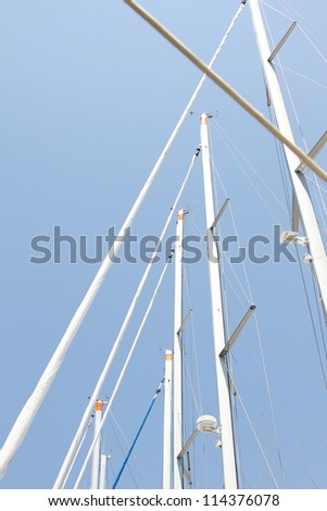 Close-up of a lot of masts against the sky, with no sails