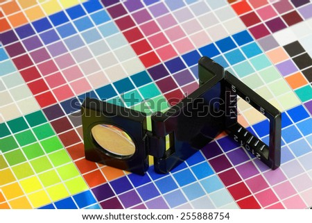 Close-up of a loupe on a multi color test print - stock photo