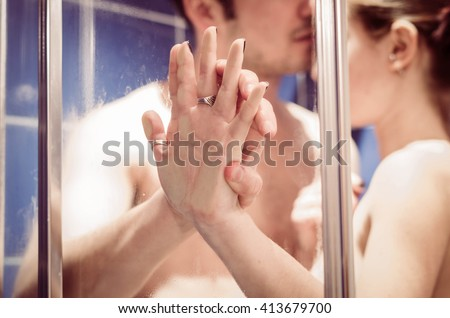 close up of a loving and caucasian couple's hands, while they are together in the shower - lifestyle and people concept  - stock photo