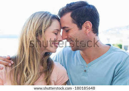 Close-up of a loving young couple with eyes closed at home - stock photo