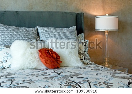 Close up of a luxury set of bedding in black and white patterns with a red accent flower on a bed in natural light - stock photo