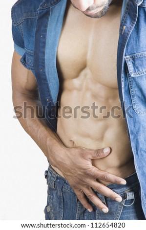 Close-up of a macho man checking his abdominal muscles - stock photo