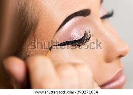 Close up of a make-up man artist getting eyeliner to model.