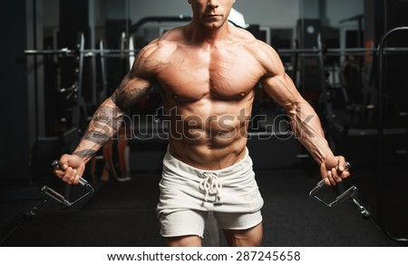 Close-up of a male bodybuilder working out at gym. Bodybuilding, posing, black background, muscles - the concept of bodybuilding. Article about bodybuilding. - stock photo