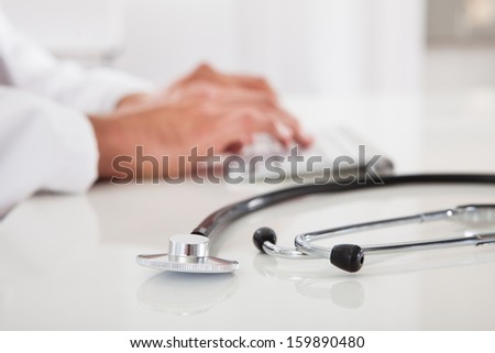 Close-up Of A Male Doctor Typing On Keyboard - stock photo