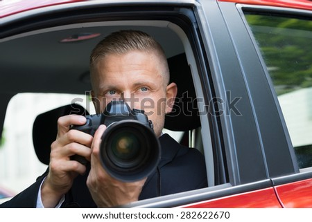 Close-up Of A Male Driver Photographing With Slr Camera From Car - stock photo