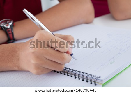 Close-up of a male hand holding a ballpen and writing in the notepad