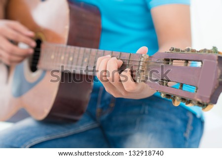 Close-up of a male hand playing the guitar - stock photo