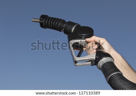 Close-up of a male hand raising fuel nozzle against blue sky