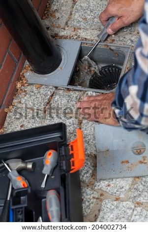 Close-up of a male hands cleaning pavement drain hole - stock photo
