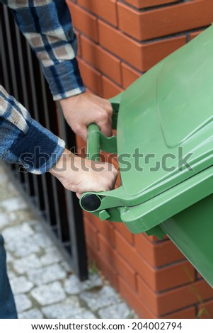 Close-up of a male hands pushing a wheeled dumpster - stock photo