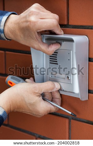Close-up of a male hands repairing intercom, vertical - stock photo