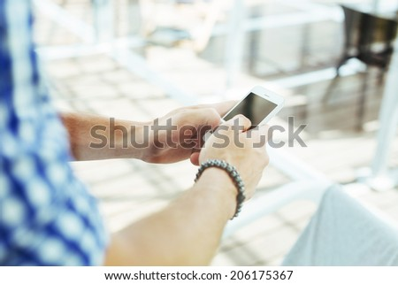 Close-up of a male hands typing a message on a smartphone