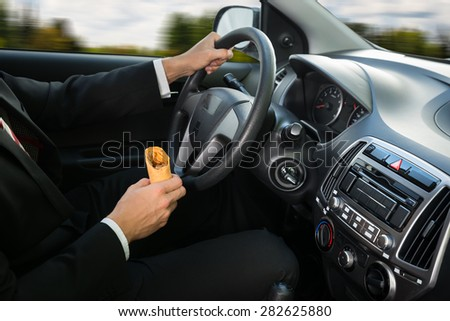 Close-up Of A Male Holding Snack While Driving In His Car - stock photo