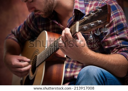 close up of a male musician playing acoustic guitar - stock photo