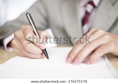 close-up of a male's hands writing down ideas.