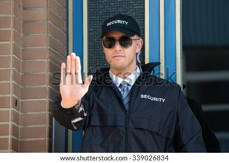Close-up Of A Male Security Guard Making Stop Sign With Hand Wearing Sunglasses - stock photo