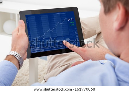 Close-up Of A Man Analyzing Graph On Digital Tablet - stock photo