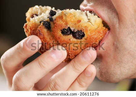 Close up of a man biting into a blueberry muffin. - stock photo