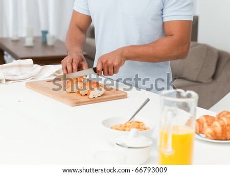 Close up of a man cutting bread during breakfast in his kitchen at home