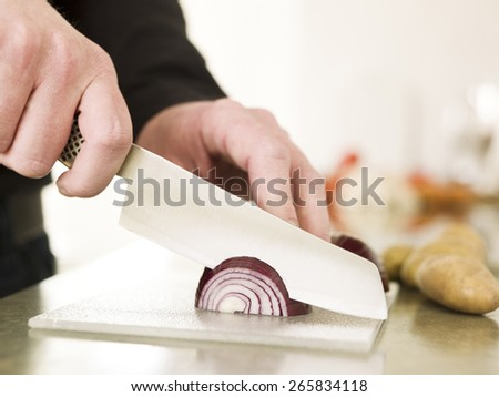Close up of a man Cutting onion with knife - stock photo