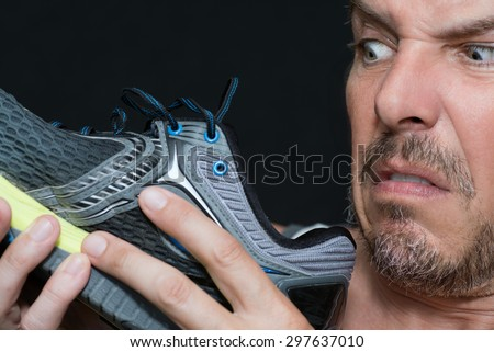 Close-up of a man disgusted by the smell of his running shoe. - stock photo