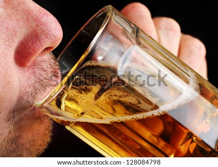 Close Up of a Man Drinking a Glass of Beer - stock photo