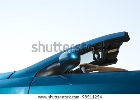 Close-up of a man driving his convertible car - stock photo