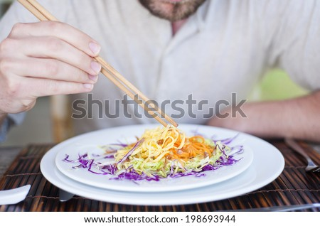 Close up of a man enjoying a meal with chopsticks in vietnamese restaurant - stock photo