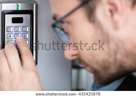 Close up of a man entering security code combination to unlock the door