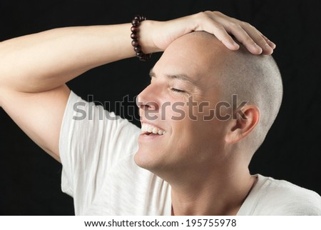 Close-up of a man feeling his newly shaved head. - stock photo