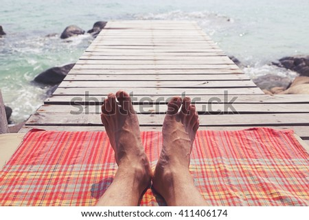 Close up of a man feet relaxing on a rustic beach terrace with the sea in the background - stock photo