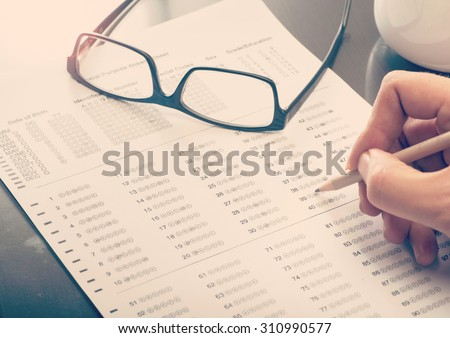 Close up of a man filling a standardized test form