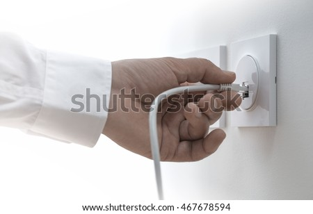 Close-up of a man hand plugging an ethernet cable into a wall socket, horizontal image. Concept of broadband network