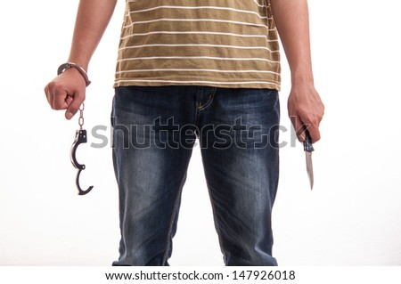 Close up of a man handcuffed with a knife in hand - stock photo