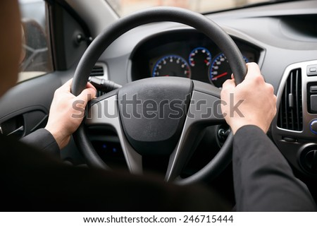 Close-up Of A Man Hands Holding Steering Wheel While Driving Car - stock photo