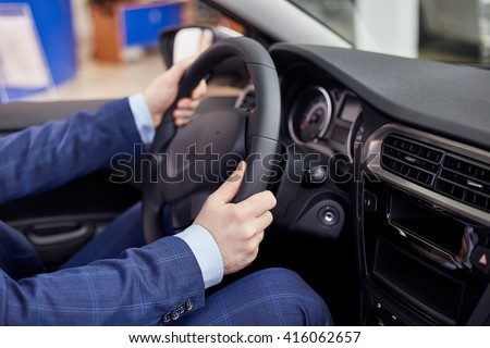 Close-up Of A Man Hands Holding Steering Wheel While Driving Car, shot inside the car