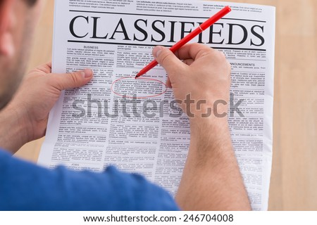 Close-up Of A Man Highlighting Advertisement On Newspaper With Red Pen - stock photo