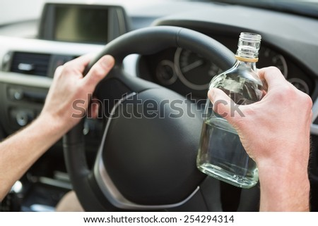 Close up of a man holding a bottle of vodka in his car - stock photo