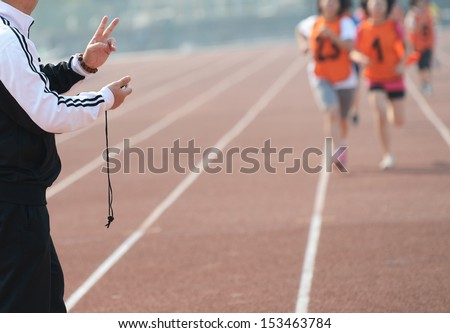 Close-up of a man holding a stopwatch to measure performances of the runners in a stadium  - stock photo