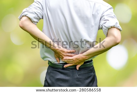 close up of a  man holding his back in pain - stock photo
