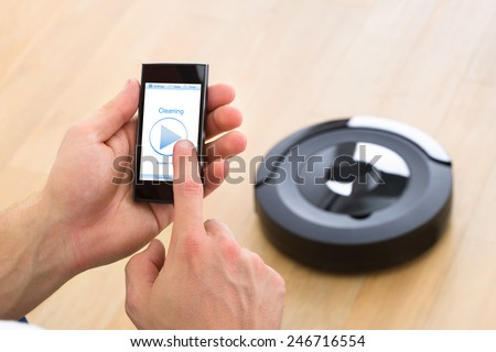 Close-up Of A Man Holding Remote Control Of Robotic Vacuum Cleaner To Start Cleaning - stock photo