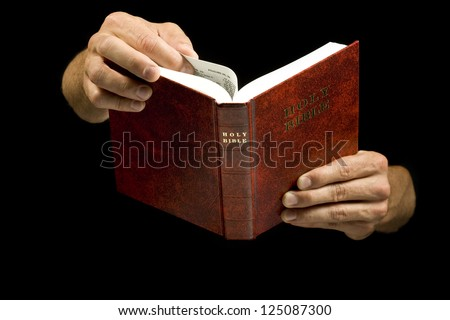Close-up of a man holding the Holy Bible - stock photo
