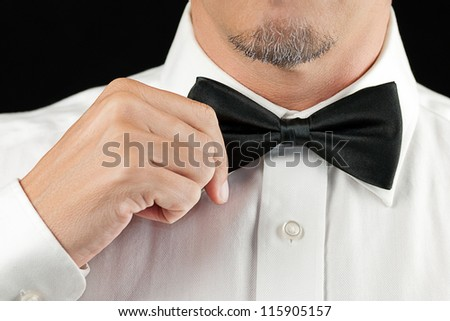 Close-up of a man in a tux straightening his bowtie, one hand, no jacket.
