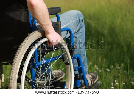 Close up of a man in a wheelchair in the park - stock photo