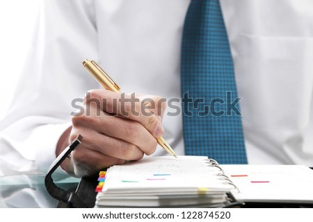 Close-up of a man in formal wear writing in his calendar