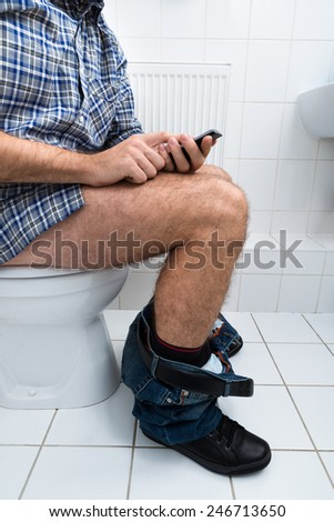 Close-up Of  A Man In Toilet Using Cellphone - stock photo