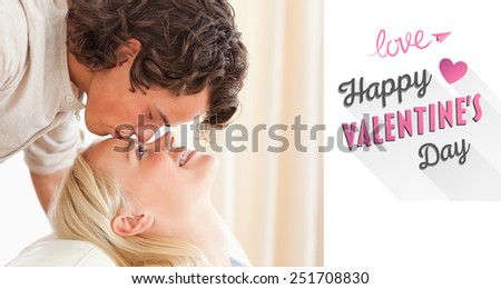 Close up of a man kissing his fiance on the forehead against cute valentines message - stock photo